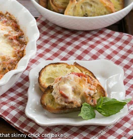 Cheesy Lasagna Dip with Sausage on a toast with a sprig of basil