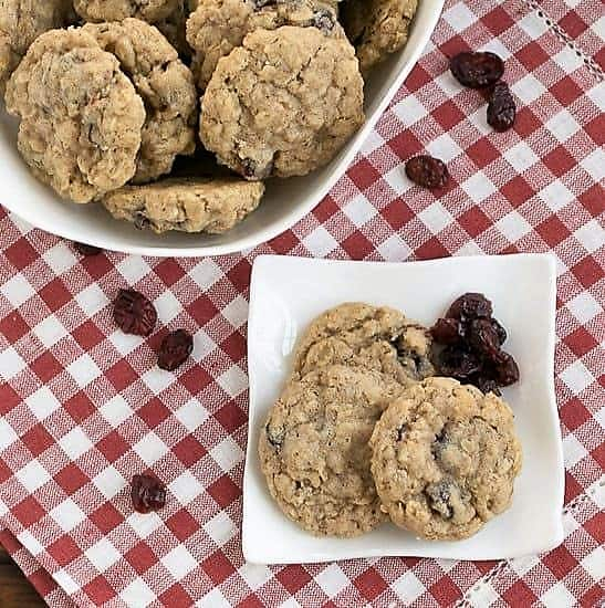 Oatmeal Craisin Cookies viewed from above on a white plate with craisns next to a white bowl full of cookies