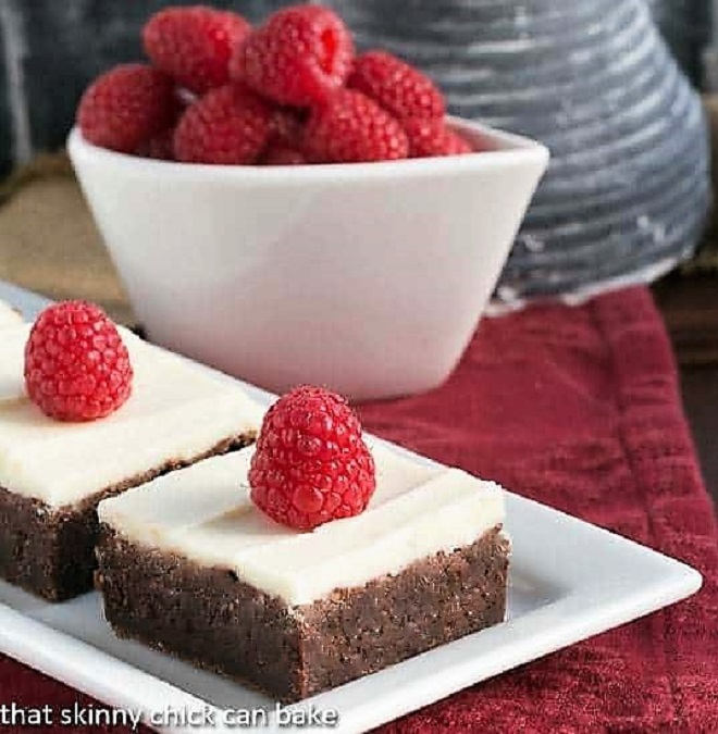 Raspberry Brownies with White Chocolate Icing on a white tray on a red napkin