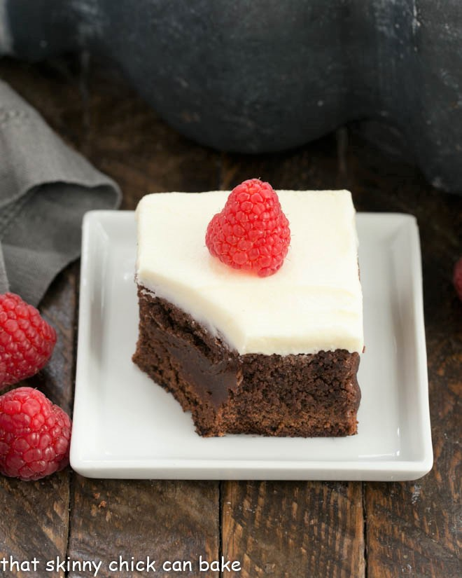 A frosted raspberry brownie on a square white plate with a bite removed