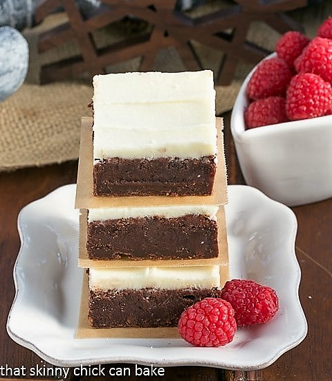 Raspberry Brownies with White Chocolate Icing stacked on a square white plate with 2 fresh raspberries