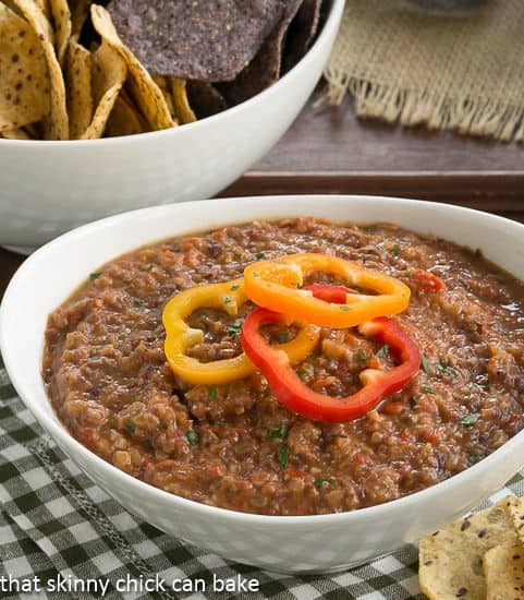 Smoky Black Bean Dip in a white bowl topped with pepper rings