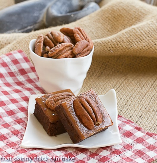 Turtle Brownies on a small white plate with a bowl of pecans
