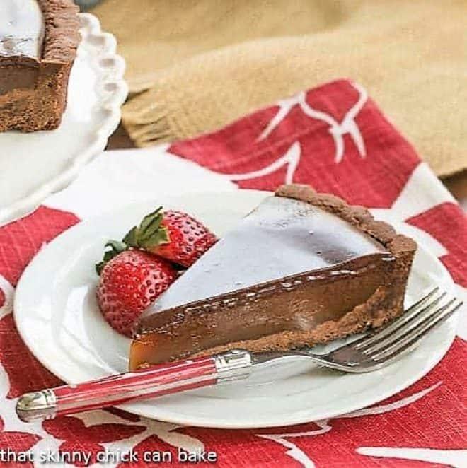 Chocolate Caramel Tart slice on a white plate