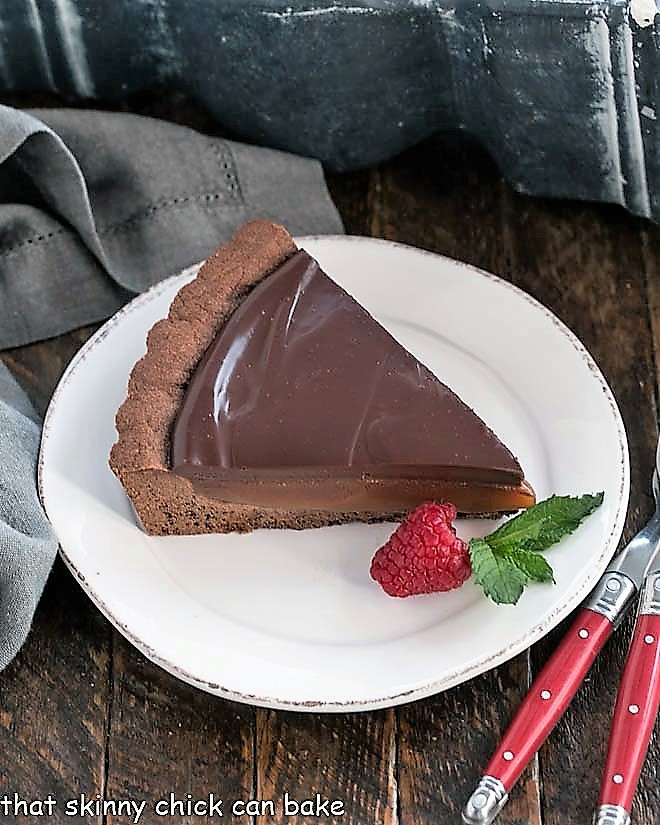 Slice of a Chocolate Caramel Tart on a white plate