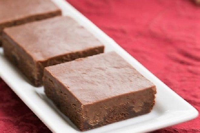 Chocolate Poke Brownies lined up on a rectangular white ceramic tray