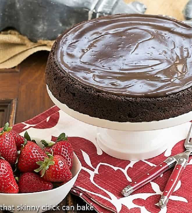 Flourless Double Chocolate Cake on a white ceramic cake stand