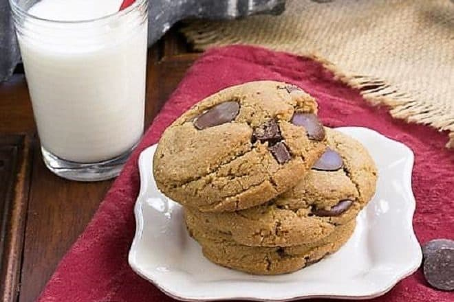 Jumbo Chocolate Chips stacked on a white square plate with a glass of milk
