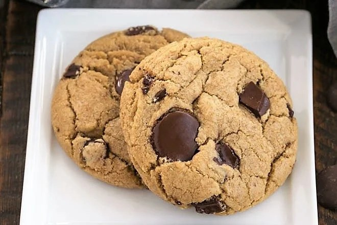 Two umbo chocolate chip cookies on a square white plate