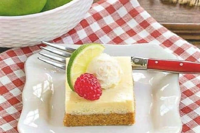 Key Lime Pie Bars on a square white plate with a lime, raspberry and whipped cream garnish