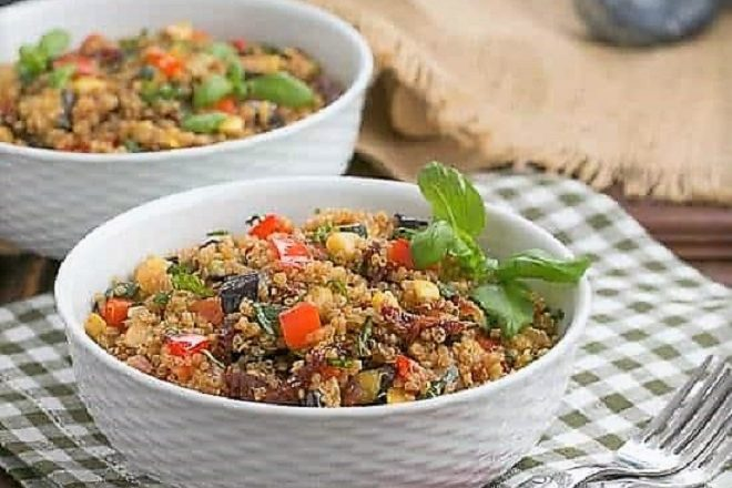 2 bowls of quinoa salad in white basketweave bowls garnished with fresh basil