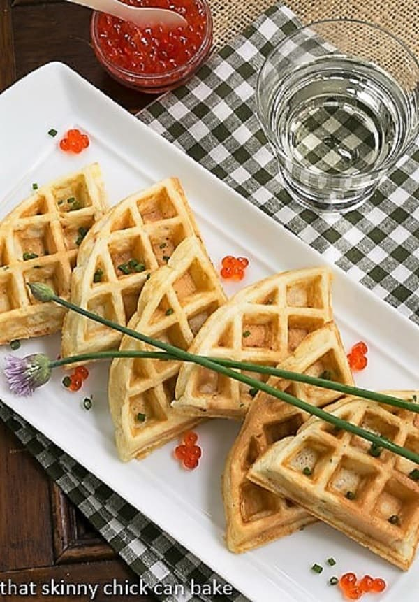 Smoked Salmon Waffles lined up on a white serving tray with chive blossoms and salmon roe