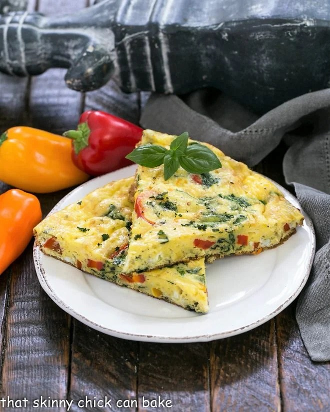 2 slices of egg frittata on a white plate with mini peppers in the background