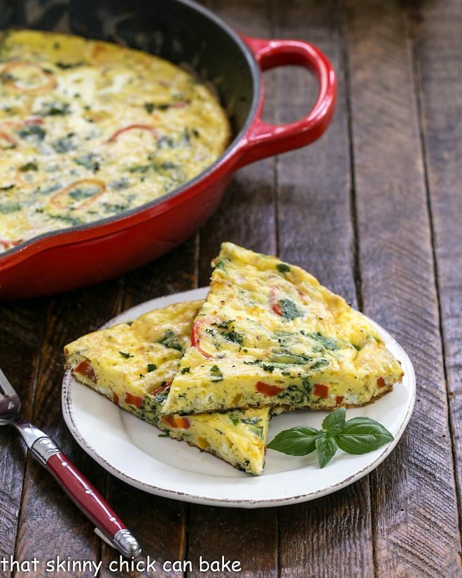 Two slices of breakfast frittata on a white plate in front of a cast iron skillet