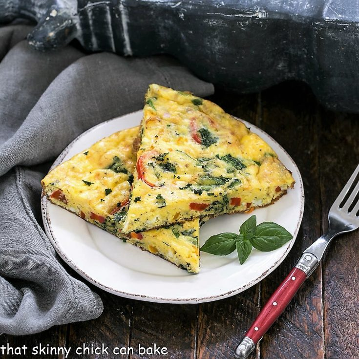 2 slices of spinach frittata on a white plate with a red handle fork