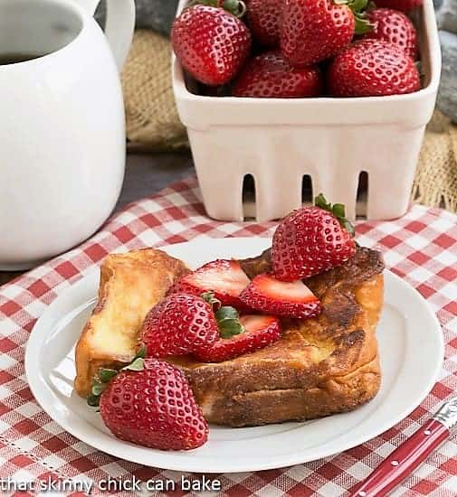 Strawberry Mascarpone Stuffed French Toast on a white plate topped with fresh strawberries