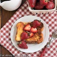 A plate of strawberry mascarpone stuffed french toast on a checkered napkin