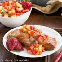 Strawberry Salsa Topped Salmon garnished with fresh strawberries on a white plate