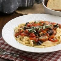 Summer Pasta Puttanesca in a white bowl with a garnish of fresh oregano
