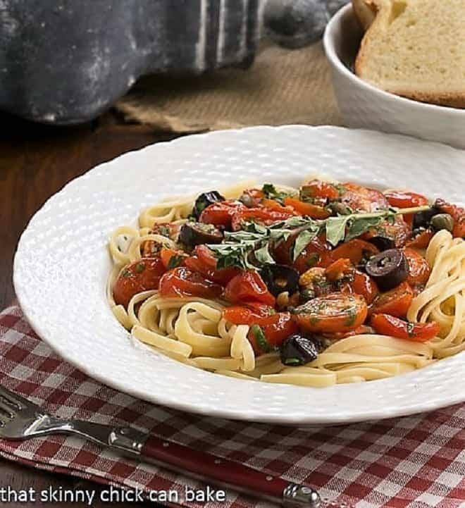 Summer Pasta Puttanesca in a white bowl with a garnish of fresh oregano