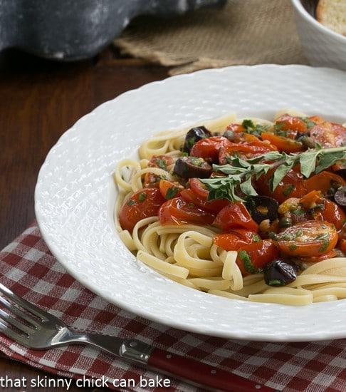 Summer Pasta Puttanesca in a white bowl over a checkered napkin