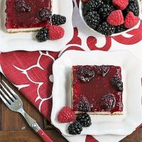 Overhead view of blackberry cheesecake bars on square white plates