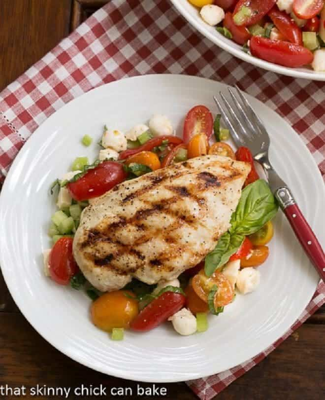 Overhead view of grilled chicken breast over a fresh Caprese salad