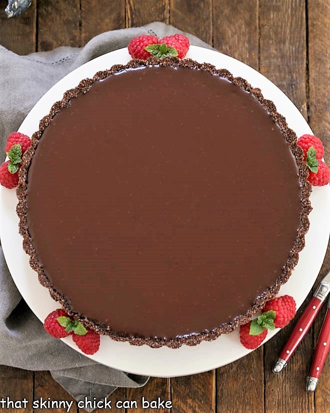 Ganache Topped Chocolate Tart overhead view on a white serving plate