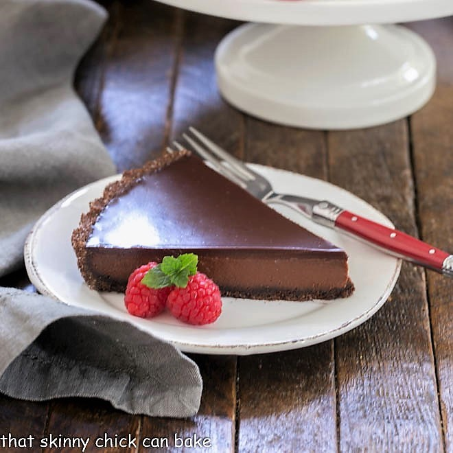 Slice of chocolate tart on a round white plate with a red fork
