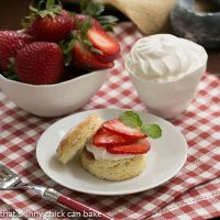 Double strawberry rose shortcake on a white plate next to bowls of strawberries and cream