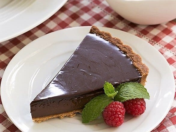 Ganache Topped Chocolate Tart on a white plate garnished with raspberries