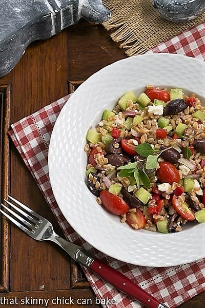 Overhead view of Greek Farro Salad in a white bowl on a red and white checked napkin