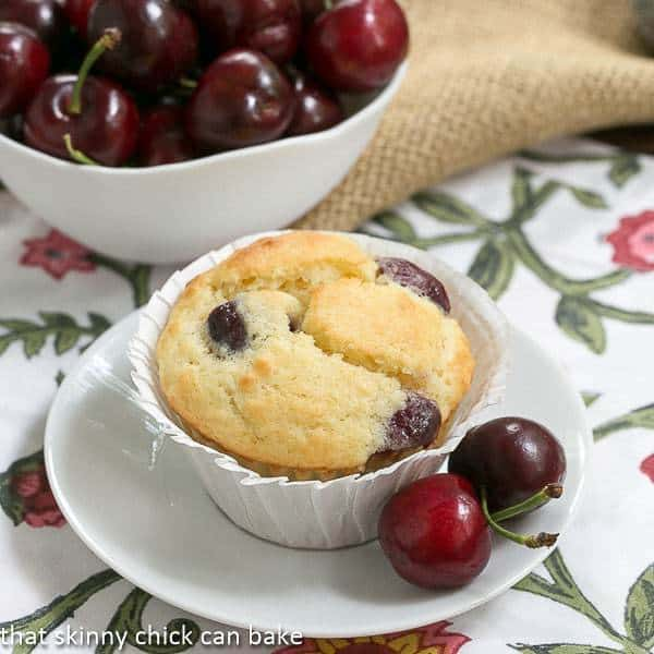 Double Cherry Muffins on a white plate with fresh cherries