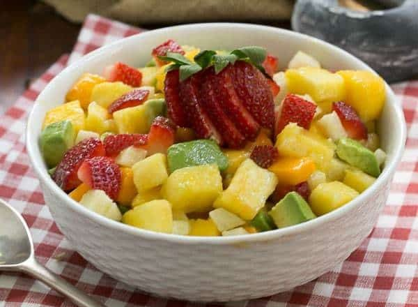 Mango Strawberry Avocado Salad in a white bowl with a silver serving spoon