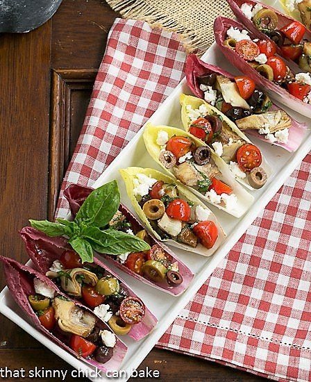 A tray of endive boats on a red and white checked napkin