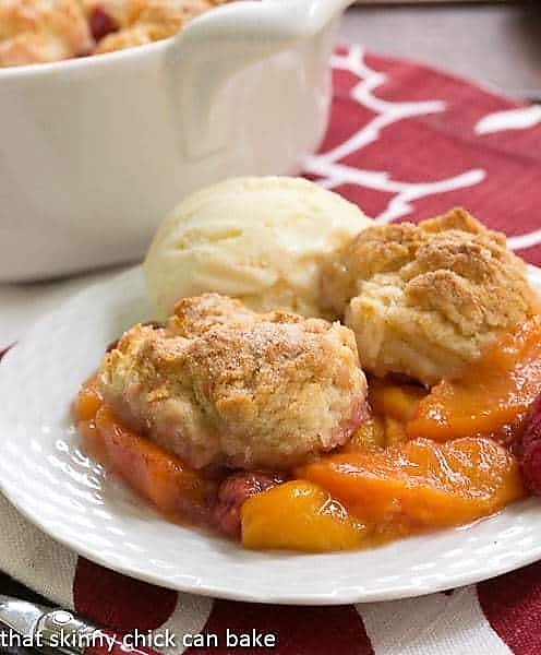Peach Raspberry Cobbler on a white dessert plate with a scoop of vanilla ice cream
