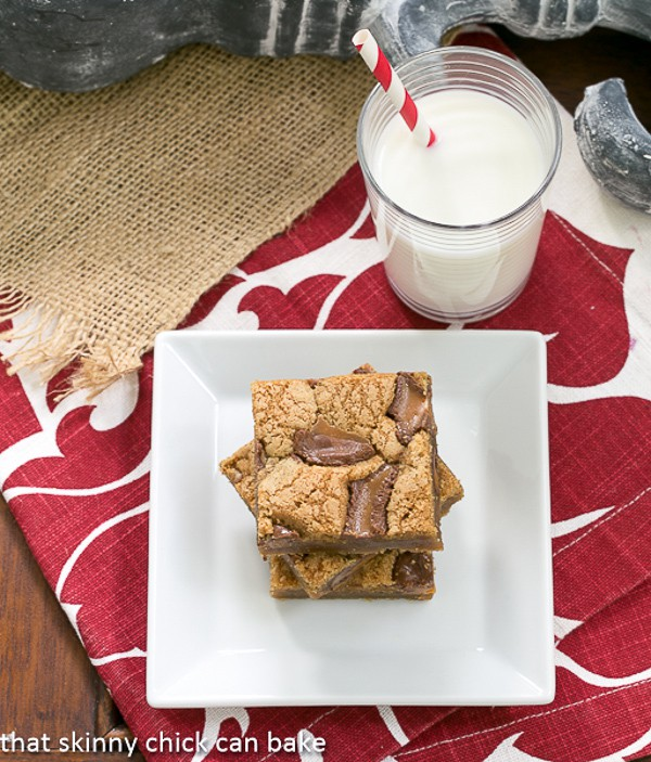 Biscoff Rolo Bars stacked on a square white plate with a glass of milk