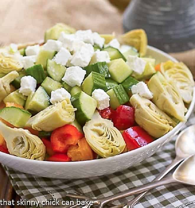 A white bowl of Greek Salad topped with feta cubes