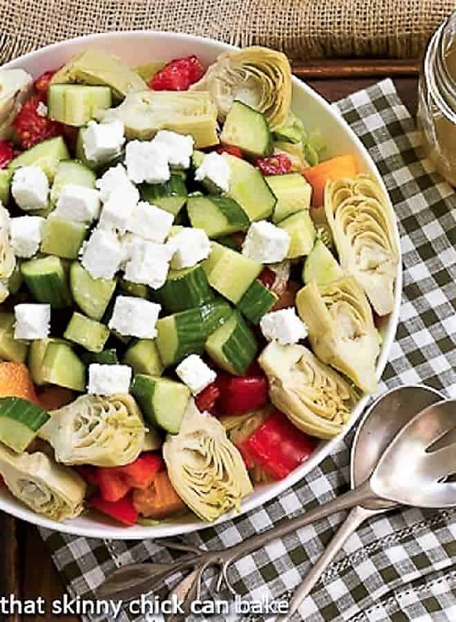 Greek Salad with Feta in a white serving bowl over a green and white checked napkin