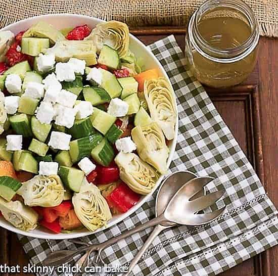 Greek Salad with Feta in a serving bowl with salad serving utensils and a jar of vinaigrette