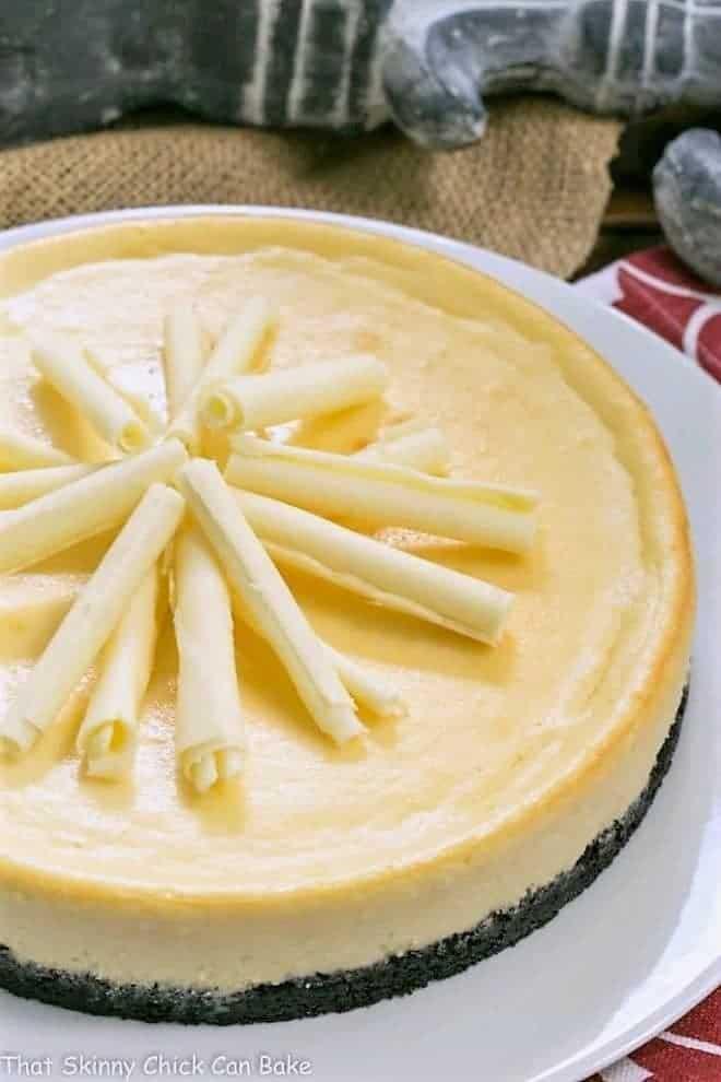 White Chocolate Frangelico Cheesecake garnished with white chocolate curls on a white cake plate