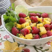 Raspberry Mango Salsa in a white bowl with cilantro and lime garnish