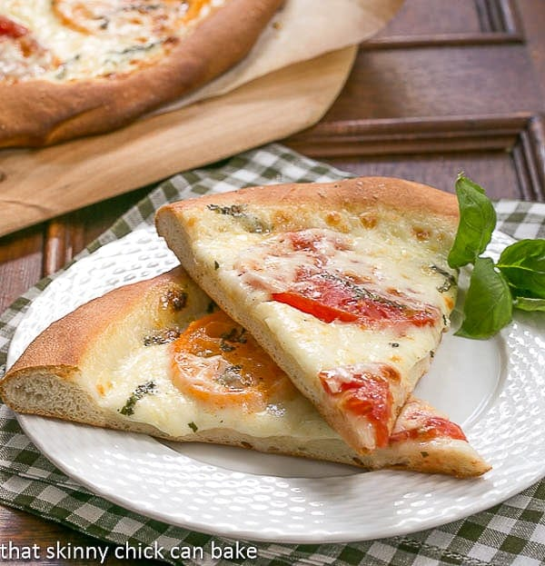 Homemade Pizza Margherita slices on a white plate