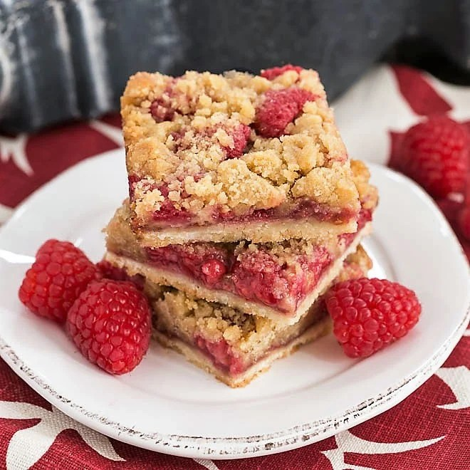 Stack of Streusel Topped Raspberry Cookie Bars on a small round white plate