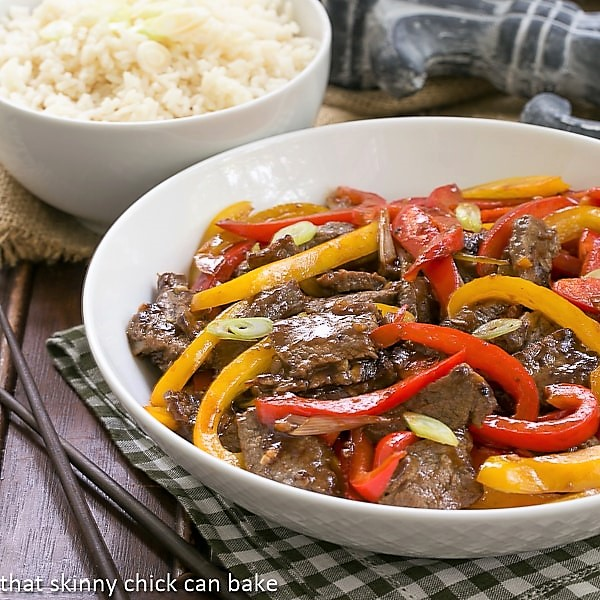 Asian Beef with Peppers in a white serving bowl with a side dish of rice