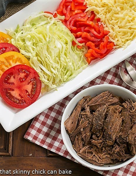 Overhead view of Slow Cooker Beef Barbacoa in a white bowl with toppings on a white tray.