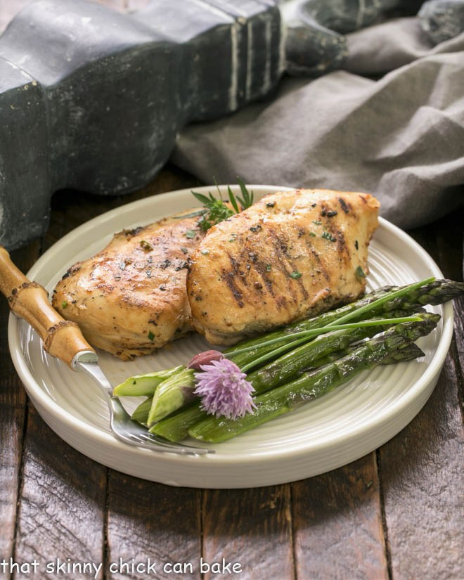 2 chicken breasts on a dinner plate with asparagus spears and a bamboo handle fork
