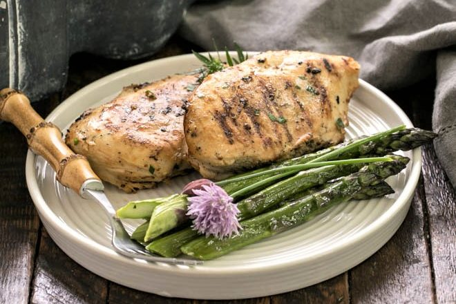 Mustard garlic lime marinated chicken on a white dinner plate with asparagus spears and a fork