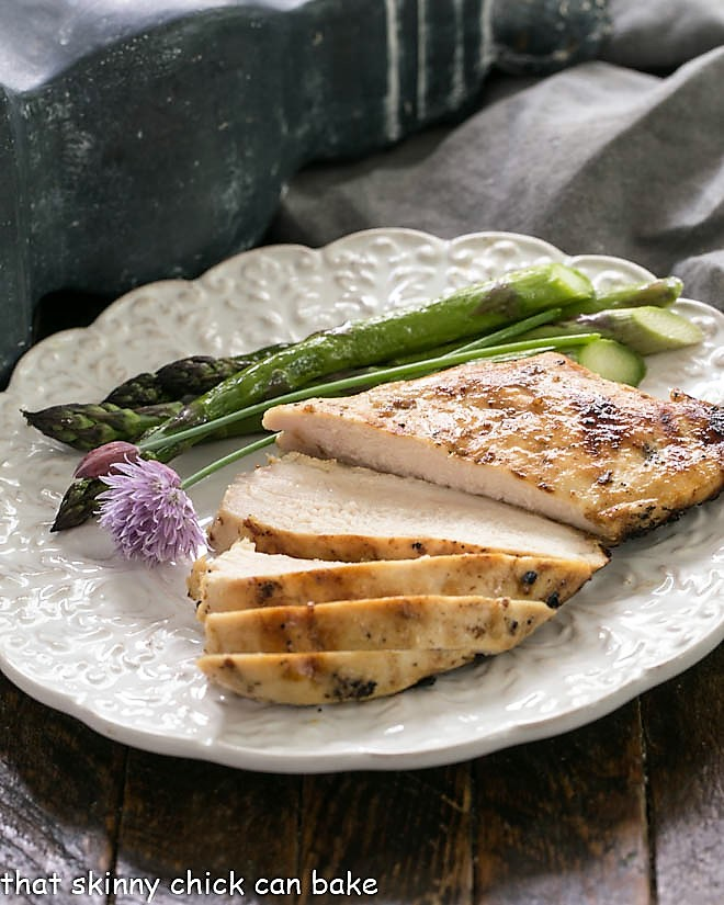 A sliced chicken breast on a white dinner plate with asparagus