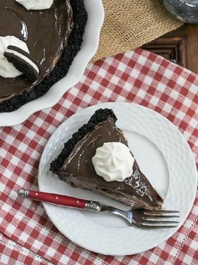 Slice of Fudge Topped Chocolate Ice Cream Pie on a white dessert plate